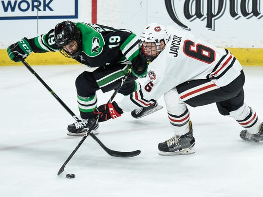 Shane Gerrsich of North Dakota and Luke Jaycox of St. Cloud State struggle for control of the puck during the first game of the NCHC Frozen Faceoff Friday, March 16, at the Xcel Energy Center in St. Paul.
