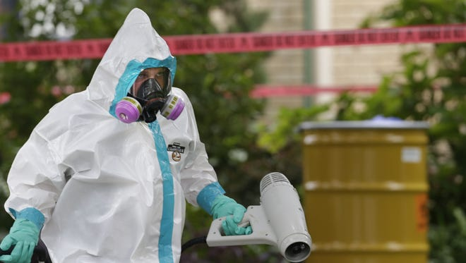 A hazmat worker cleans outside the apartment building of a hospital worker on Oct. 12, 2014, in Dallas.