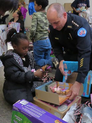 Pensacola Police Chief Chip Simmons helps Arriyah Fox, 6, open one of her presents during the sixth annual Pensacola Police Department Christmas Party on Wednesday made possible by a grant from the Kugelman Foundation.