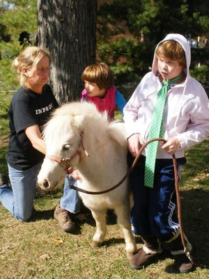 Blue Ash resident Ingrid Anderson is seen with her children. She is suing the city of Blue Ash for not allowing her daughter to her miniature horse as a service animal.