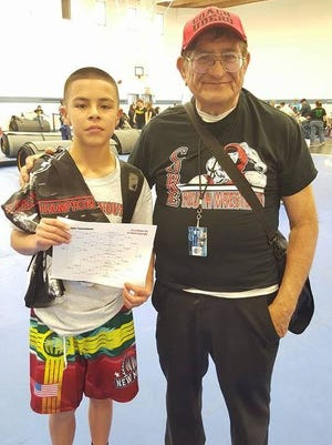 Cobre Youth Wrestling's Jacob Maes poses with his coach Ruben Udero after winning a state title in Socorro.