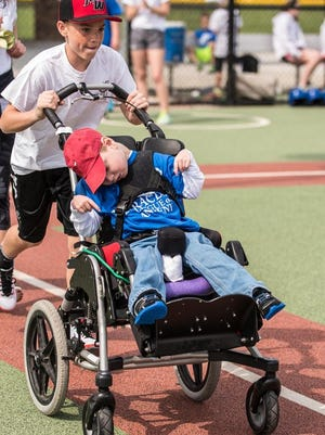 Ankeny Miracle League player James Haugh is pushed along the base path by an Angel in the Outfield volunteer.