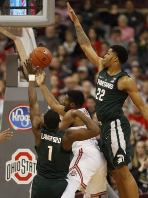Ohio State guard JaQuan Lyle goes up to shoot between Michigan State's Joshua Langford, left, and Miles Bridges during the first half in Columbus, Ohio, Sunday,