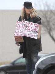 A woman panhandles near Glenstone Avenue in March 2014.