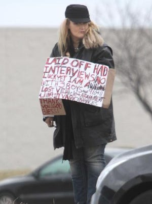 A woman panhandles in Springfield, Missouri, in March 2014.