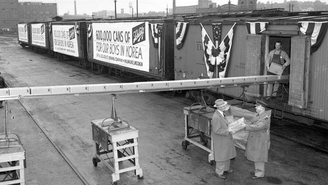 Boxcars decorated in patriotic bunting and loaded with 600,000 cans of Schlitz beer start on their way to Korea, in this photo published Sept. 28, 1950, in The Milwaukee Journal. The beer was a gift to U.S. soldiers fighting in Korea from Milwaukee-based Jos. Schlitz Brewing Co. Erwin C. Uihlein (left), president of Schlitz Brewing, handed the first case to Col. John F. Ehlert, chief of the Wisconsin military district. Ehlert marked the first case for Lt. Gen. Walton Walker, commander of the U.S. 8th Army. Loading the beer is Solomon Siegel, a Schlitz employee.