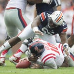 Auburn Tigers defensive lineman Carl Lawson jumps on Ole Miss quarterback Chad Kelly as he recovers a fumble. Lawson is a draft-eligible third-year sophomore.