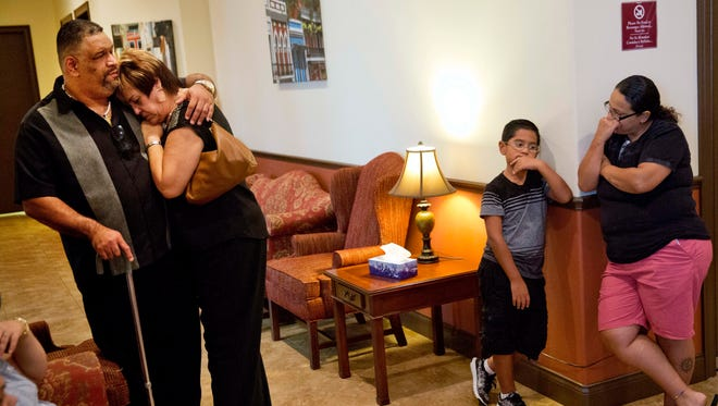 Rafael Rivera, left, comforts Jeannette Gonzalez, as they mourn the loss of Eric Ivan Ortiz-Rivera, one of the victims killed in the Pulse nightclub mass shooting, inside a funeral home during his wake Thursday