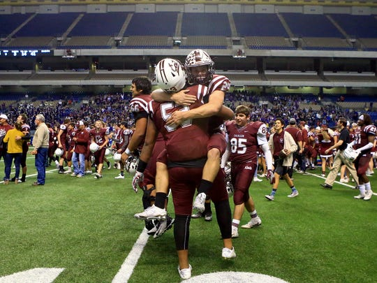 Calallen's Rayce Deal (back) and Kenese Leomiti  celebrates after defeating College Station in the Class 5A Division II state semifinal Friday, Dec. 9, 2016, at the Alamodome in San Antonio.