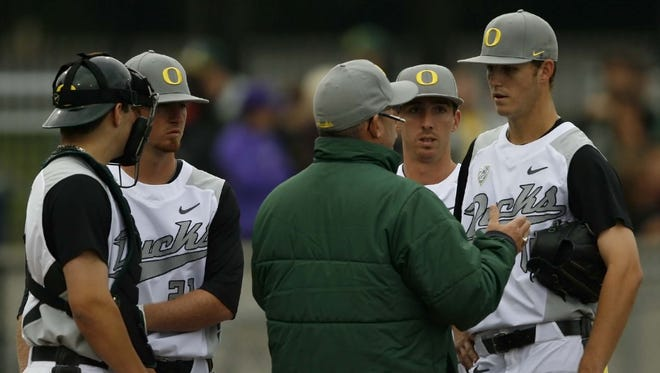 Oregon starting pitcher Cole Irvin (right) listens to head coach George Horton (center) during the Ducks' 9-0 loss to Oregon State in a Civil War baseball game at PK Park, in Eugene, on Saturday, May 18, 2013.