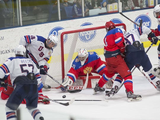 Grant Mismash of the NTDP Under-17 team (No. 46) tries to jam the puck past Russia goalie Maxim Zhukov.