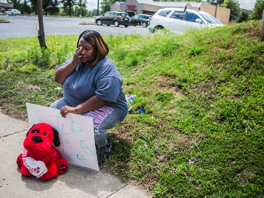 "June 14, 2017 - Danielle Jones, a mother of four, wipes away tears as she holds a ""Stop the Violence"" sign as she sits across the road from a Subway located at 6744 Winchester Rd., to give her condolences to Laylah Washington's family on Wednesday morning. Jones also brought with her a red stuffed animal that had ""Kiss Me"" written on a heart against its chest.  ""I'm out here to show my condolences and support to the family of Laylah Washington 'cause this could have been my child. This is my child because I'm part of the community,"" Jones said. ""It was senseless, just senseless. I pray to God they catch the coward who took this child's life.""  Washington, 2, died Tuesday night after suffering from a gunshot wound to the head from an apparent road rage incident on Sunday.  ""What happened to fighting and standing up and being a man?,"" Jones asked. ""That makes you a man when you fight with your hands, not with a gun. A coward can pick up a gun."""