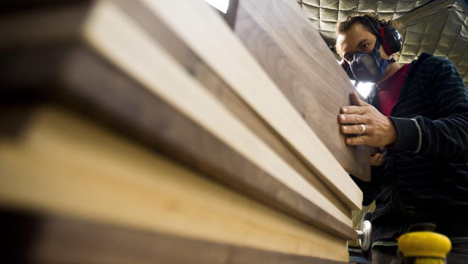 Travis Herben of Lincoln buffs out hand-made cutting boards at Vermont Farm Table's woodshop in Bristol.
