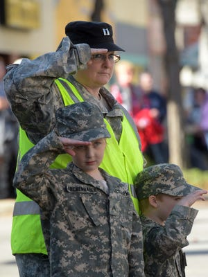 Indiana Guard Reserve Capt. Stanna Kirchenbauer salutes with Tegan Roland and Aadyn Roland during the 2016 Veteran's Parade through downtown Richmond.