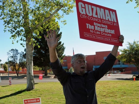 Richard Hall, a candidate for the District 4 seat on the Las Cruces City Council, holds a sign Tuesday for a candidate running for a different council seat — District 1's Eli Guzman — in front of the Branigan Library. Hall's wife Lupe stands nearby holding a sign promoting her husband's candidacy.