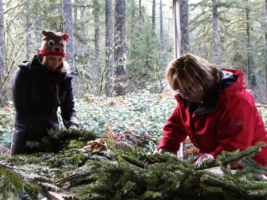 Mother and daughter Chelsia Straight and Cathy Youngern sift through piles of leaves and twigs while creating their own Christmas wreaths at the  39th Annual Silver Falls State Park Christmas Festival on Saturday, Dec. 10.