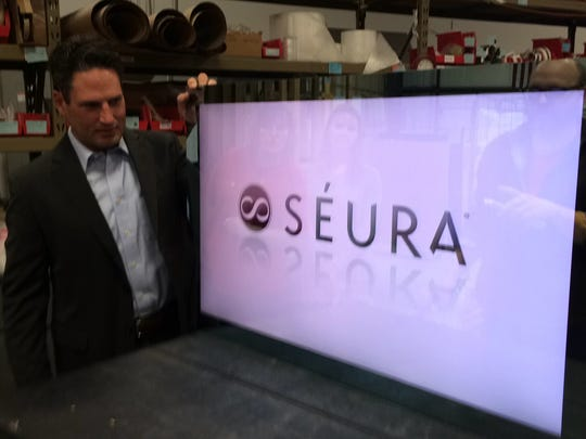 Seura co-founder Tim Gilbertson shows off one of the TV mirrors that continues to grow in popularity. Seura will more than double its manufacturing space this spring.