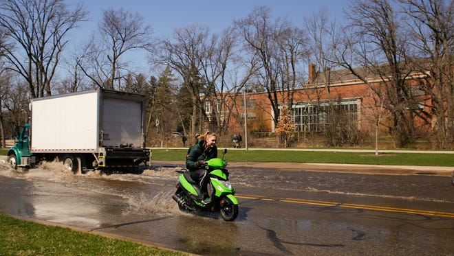 A girl on a moped scoots her way through flooded streets Friday, April 7, 2017, on the campus of Michigan State University.