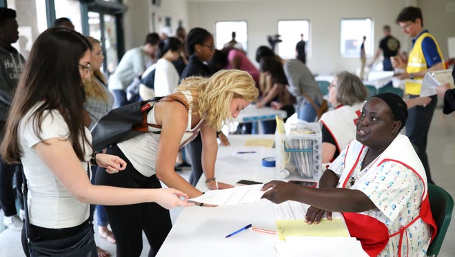Valarie Fletcher, right, a volunteer from Sail High School works to check in students who are acting as evacuees, participating in shelter and hurricane preparedness training at Lincoln High School on Thursday, June 14, 2018.