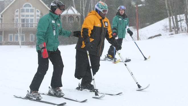 From left, Adaptive Sports Foundation volunteer instructor Dave Nichols and Mike McHugh, right, help wounded veteran Chris Gordon down the hill at Windham Mountain on Friday.