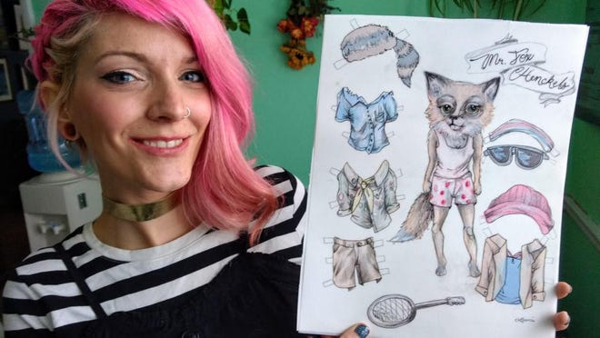 Kat Francis holding a Mr. Fox paper doll she created.