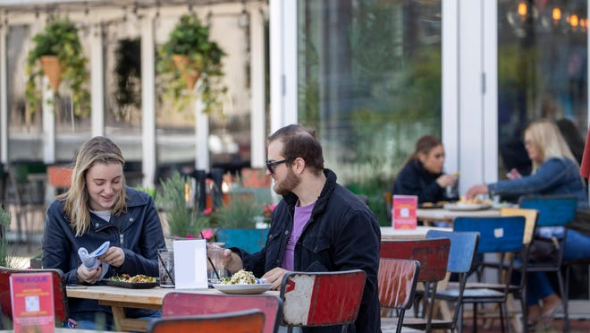 Emily Black, left, and Adam Weinstein have lunch on the outdoor patio of Mexicue restaurant, Wednesday, May 20, 2020, in Stamford, Conn. Restaurants can begin offering service in outdoor dining areas as part of the first phase of Connecticut's statewide reopening.
