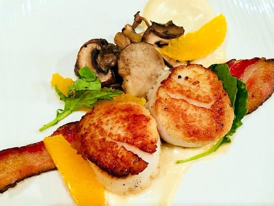 Scallops with bacon, a cauliflower puree and an orange