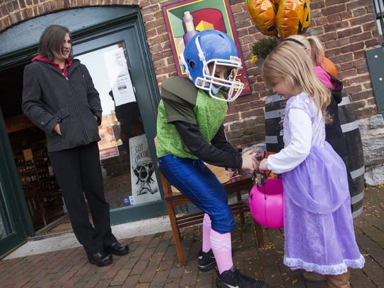 Aidan Artly hands out candy to Emily Edson and other