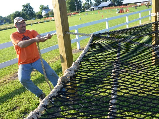 Dean Colony tugs on a rope Tuesday to tighten up the spider web play net at Colony Pumpkin Patch in North Liberty.