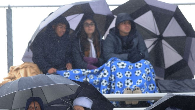 Soccer fans at Oxnard College take cover under umbrellas during a recent Saturday game.