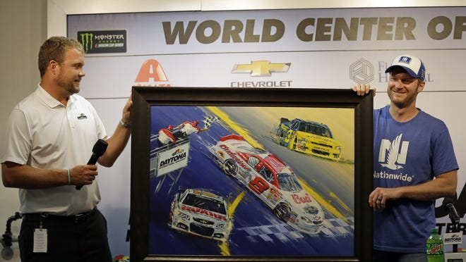 Chip Wile, left, president of International Speedway Corporation, presents Dale Earnhardt Jr. with a painting during a news conference at Daytona International Speedway on Friday.