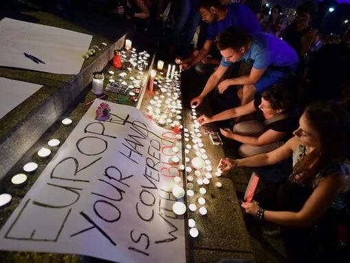 People light candles next to banner reading 'Europe,