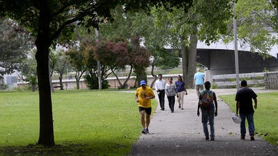 People walk and run on the River Trail recently just north of downtown Lansing in June. Ingham County is looking into ways to best spend a parks millage approved in November.