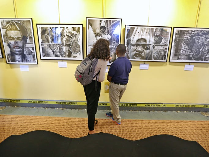 "Crispus Attucks students Teague Brewer, left, and Christ Wilson discuss the thought-provoking art of traveling art exhibit, ""Kin Killin' Kin,"" at Central Library, Tuesday, August 12, 2014."