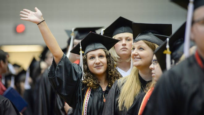 Graduates from the University of Cincinnati wave to their parents during the 197th Spring Commencement Saturday .