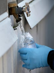 A contractor for the Cabot Oil & Gas Corp. collects a water sample from a resident's home in Dimock, Pa.  on Feb. 13, 2012