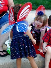 Laylah Collins (left, back to camera), 3, and her sister, Joselyn Zabala, 4, sport red, white and blue wings for the Humboldt Park Fourth of July parade.