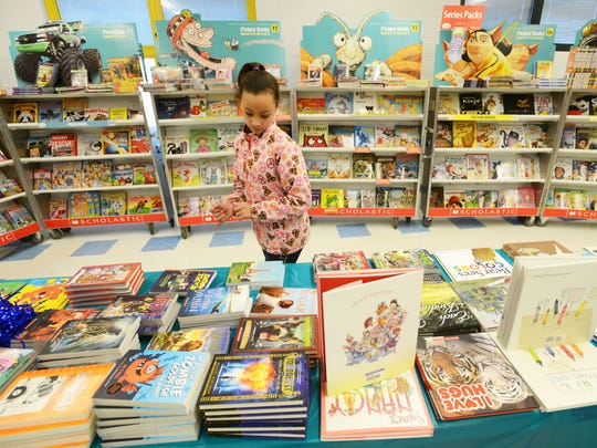 Shauneece Brandon, a fourth-grader at Zane Gray Elementary School, looks at books for sale at the school's book fair. The school is hoping to encourage students to read books about a variety of ethnicities.