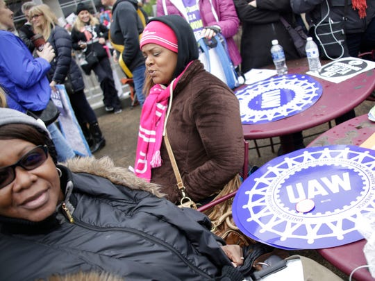 Felicia Hollins of Detroit representing UAW Region 1A, left and Nakia Stephens, 40 of Romulus take a seat during the Women's March on Washington on Saturday, Jan. 21, 2017.