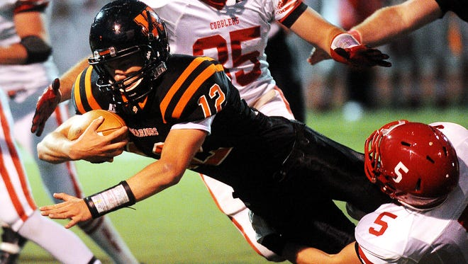Washington's Jack Schelhaas is brought down by Rapid City Central's Nate Atherton during a game at Howard Wood Field in Sioux Falls in 2013.