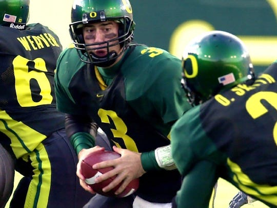 Former Oregon quarterback Joey Harrington prepares to hand off to running back Onterrio Smith during the Civil War game against rival Oregon State in 2001. AP file --Oregon quarterback Joey Harrington prepares to hand off to running back Onterrio Smith during the Civil War game against rival Oregon State in Eugene, Ore., Saturday, Dec. 1, 2001. Harrington is in the running for this year's Heisman Trophy.