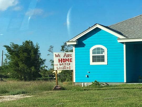 """A sign in a neighborhood just outside Rockport city limits warns looters the occupants are """"locked and loaded."""""""