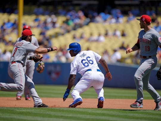Cincinnati Reds shortstop Eugenio Suarez, left, gets ready to tag out Los Angeles Dodgers' Yasiel Puig, center, as first baseman Joey Votto, right, backs him up after Puig was caught between first and second during the second inning of a baseball game, Sunday, Aug. 16, 2015, in Los Angeles.