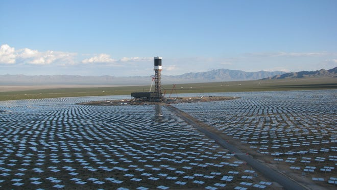 A 459-foot tall solar tower, surrounded by thousands of reflecting mirrors, at Ivanpah solar project in east San Bernardino County.
