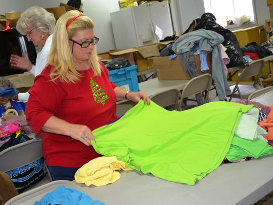 Volunteer Tonda Malone checks a donated shirt for stains and tears before putting folding it and marking its size with a sticker. Malone travels an hour and a half from her home south of Upper Sandusky each week to help at the Clothing Room.