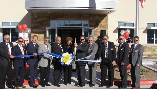TFCU CEO Max Villaronga, with scissors, cuts the ribbon March 21 at the grand opening of the credit union's new operations center at 1241 Pullman Drive in East El Paso. Members of the TFCU board of directors hold the ribbon.