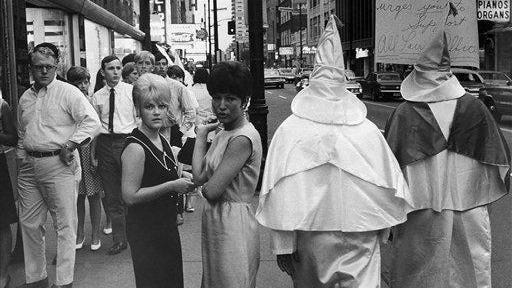 "Two robed members of the Ku Klux Klan walk in downtown in Louisville, Kentucky, June 18, 1967, in a membership drive and to oppose an open housing ordinance. Both refused to give their names, but the man on right identified himself as an ""Exalted Cyclops"" from Indiana."