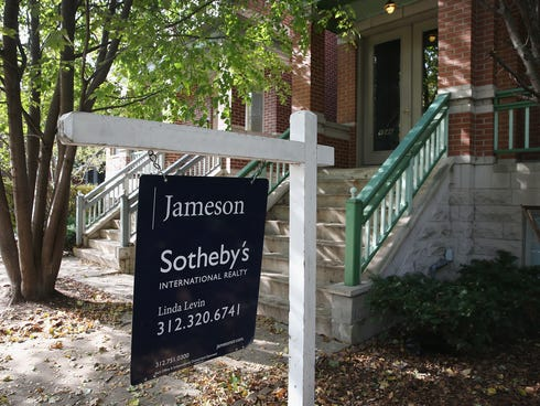 A real estate sign stands in front of a home in the Wicker Park neighborhood in Chicago.