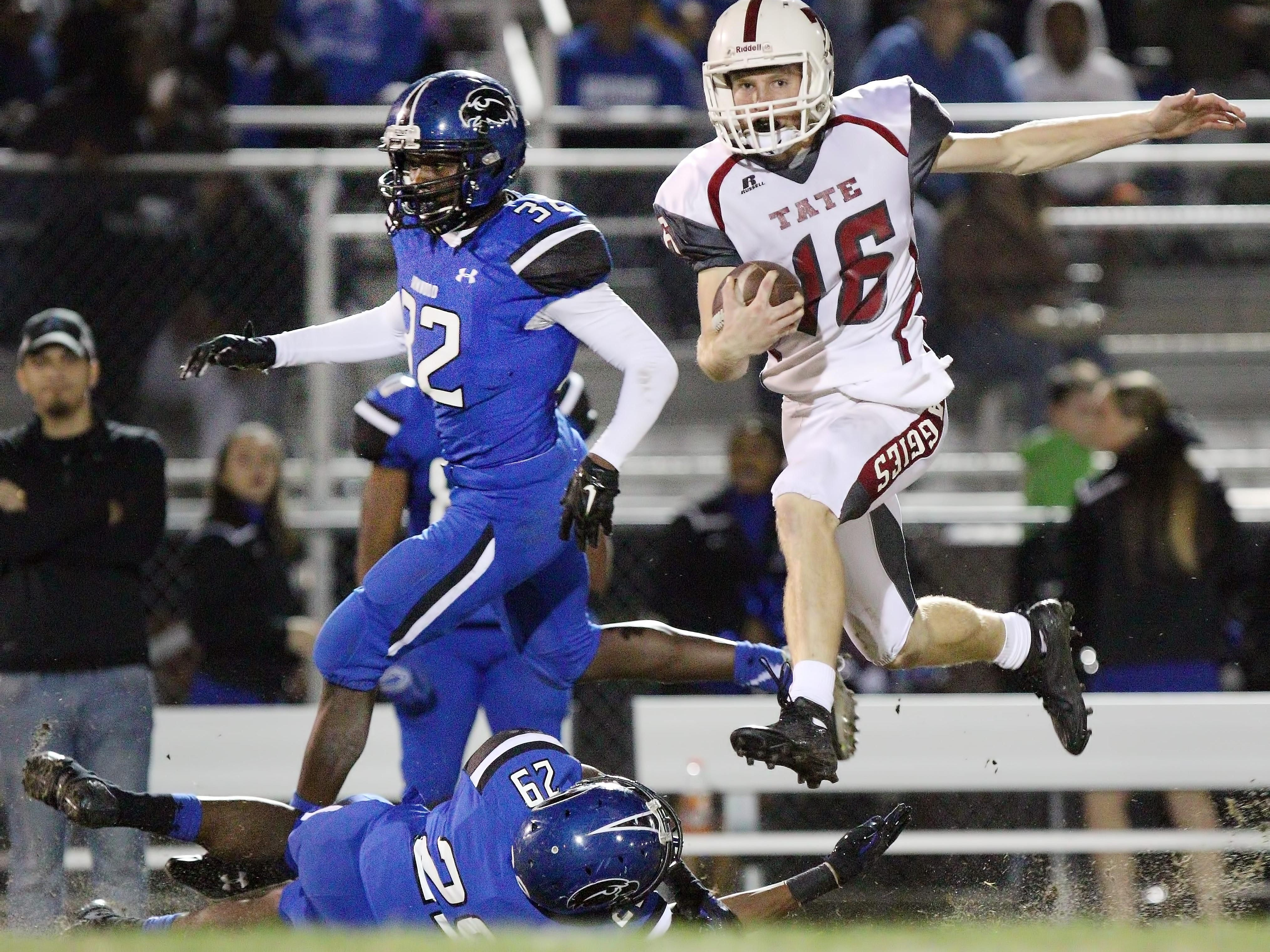 SEFFNER, FL. 12/4/2015 -- Tate receiver Jake Henry hurdles over Armwood defensive back Deon Morgan for one of the Aggies' few long gains in Friday's Class 6A state semifinal game at Lyle Flagg Field. The Aggies fell to the Hawks 53-19. Photo by BILL WARD/PNJ