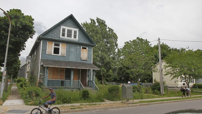 In this file photo, grass grows out of control at a foreclosed house on N. Union St. and detracts from the city neighborhood.